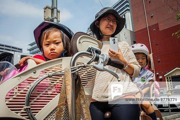 mother and children waiting for look the Sanno Matsuri parade,  near the Ichigaya station.The parade begins and ends at HieJinja shrine,  Nagata-cho.Tokyo city,  Japan,  Asia.