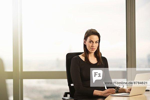 Porträt einer jungen Geschäftsfrau  die am Schreibtisch sitzt