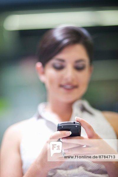 Junge Geschäftsfrau SMS auf dem Handy im Büro