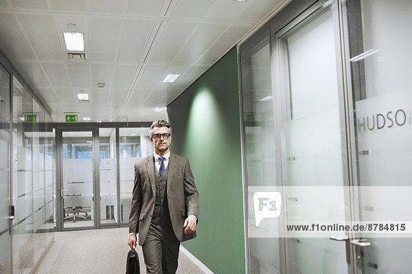 Selbstbewusster  reifer Geschäftsmann  der den Büroflur entlanggeht.