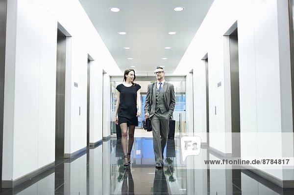 Geschäftspartner gehen den Büroflur entlang
