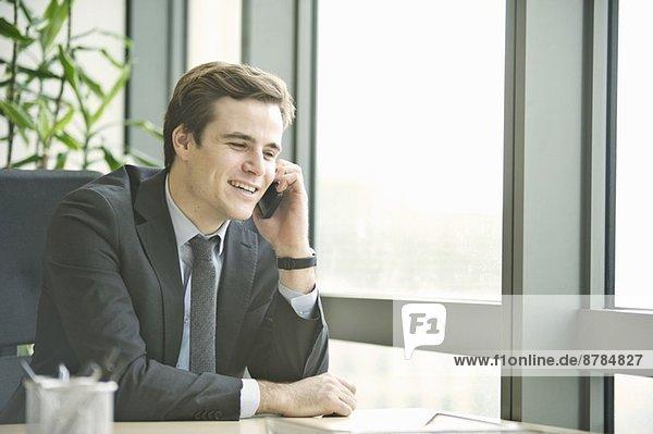 Junger Geschäftsmann im Gespräch mit dem Smartphone aus dem Büro