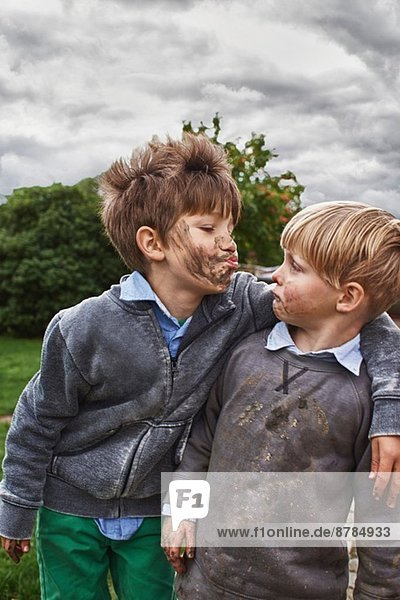 Brothers with muddy faces  arm around
