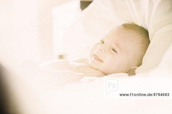 Lächelnder Junge in der Wiege liegend
