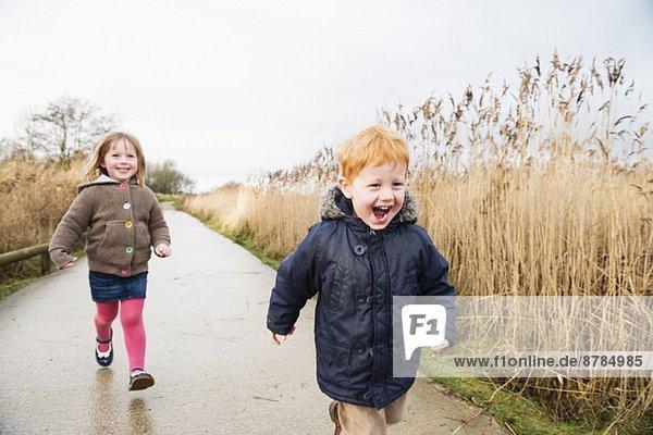 Junge Schwester und Bruder auf der Landstraße unterwegs