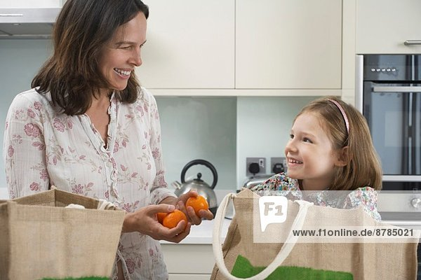 Mother and young daughter unpacking shopping bags