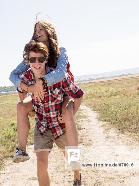 Man giving woman piggy back on dirt track