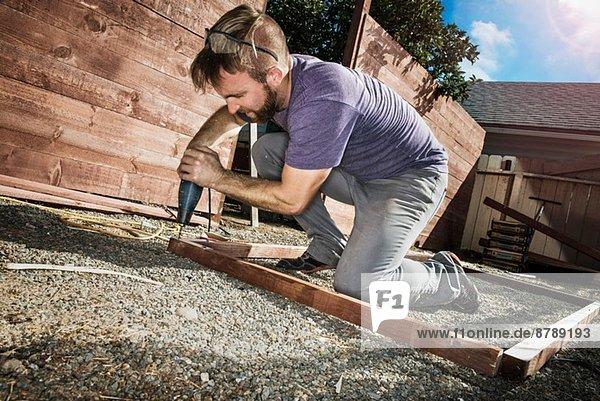 Tischler im Hinterhof bohren Holzrahmen