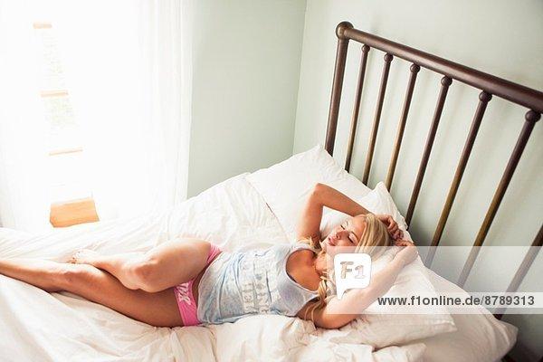 Junge Frau auf dem Bett liegend entspannend