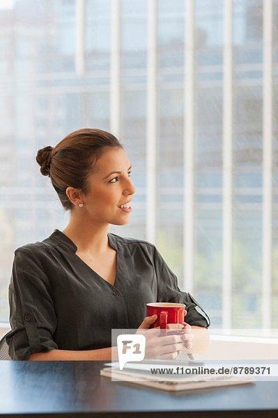Junge Geschäftsfrau bei einer Kaffeepause im Büro