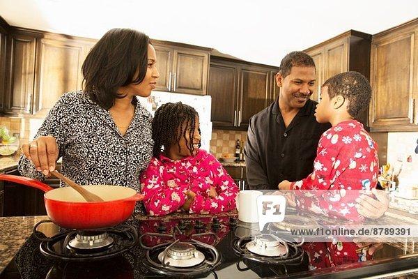Mittleres erwachsenes Paar und Kinder bei der Zubereitung des Frühstücks