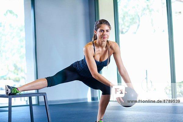 Junge Frau trainiert mit Medizinball