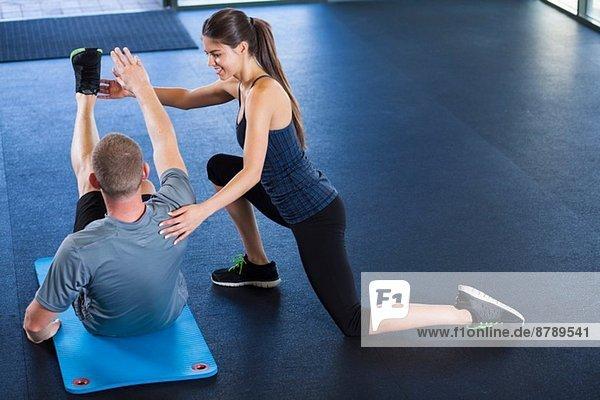 Ein Paar hilft sich gegenseitig im Fitnessstudio.