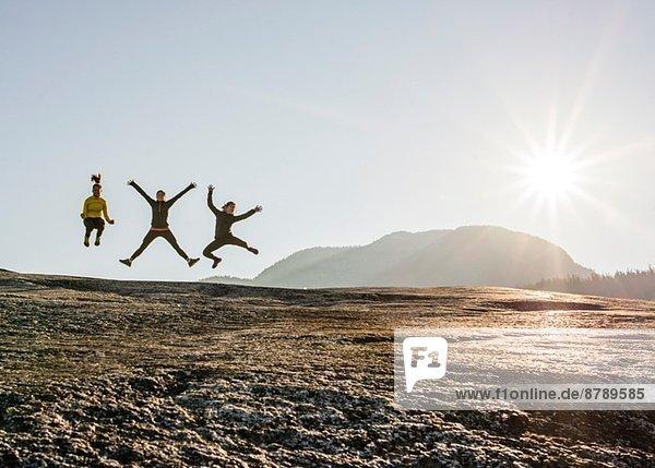 Drei junge Wanderinnen springen in der Luft auf dem Felsen  Squamish  British Columbia  Kanada