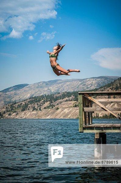 Junge Frau beim Sprung in den Okanagan Lake  Naramata  British Columbia  Kanada Junge Frau beim Sprung in den Okanagan Lake, Naramata, British Columbia, Kanada
