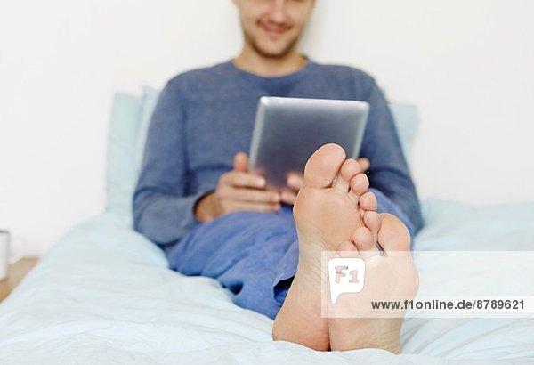 Mittlerer erwachsener Mann auf dem Bett liegend mit digitalem Tablett