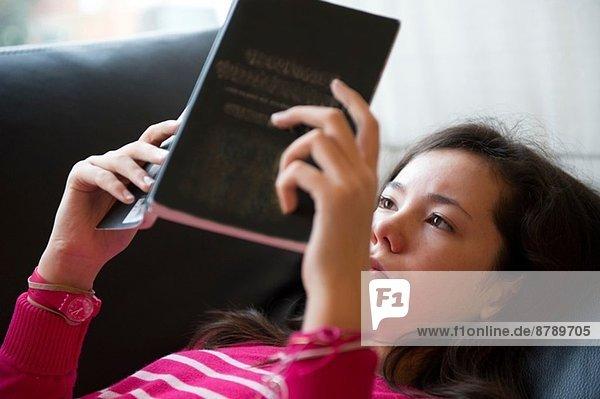 Mädchen auf Sofa liegend,  Lesebuch, Mädchen auf Sofa liegend,  Lesebuch