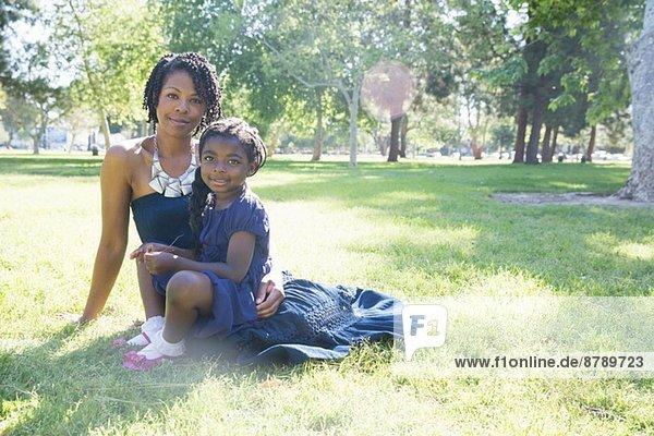 Porträt einer reifen Frau und einer Tochter  die im Park sitzen