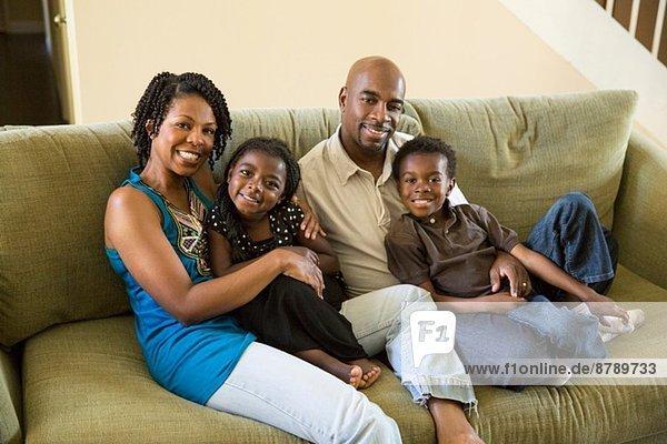 Porträt eines reifen Paares mit Sohn und Tochter auf dem Sofa
