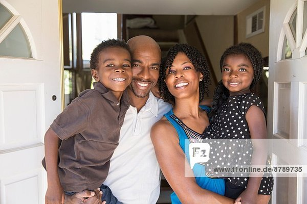 Porträt eines reifen Paares mit Sohn und Tochter vor der Haustür