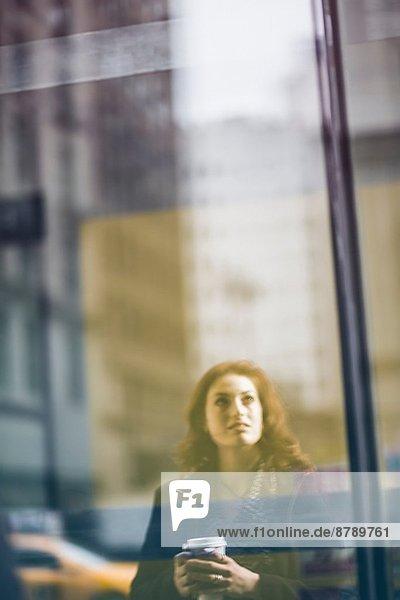 Junge Frau reflektiert im Schaufenster