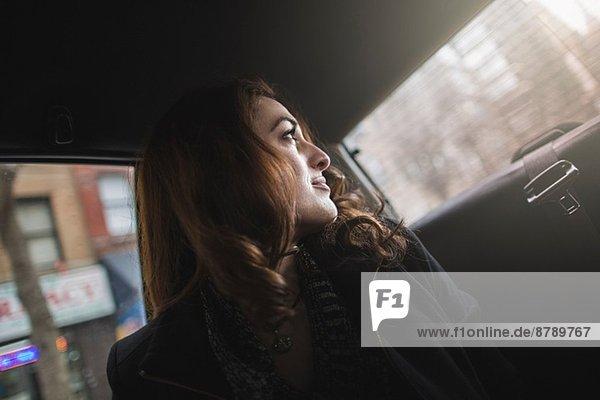 Junge Frau schaut sich vom Taxi aus über die Schulter