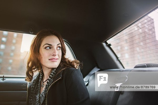 Young woman looking back from taxi