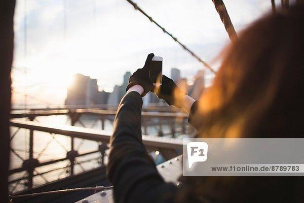 Junge Frau fotografiert Stadt auf Smartphone  New York  USA Junge Frau fotografiert Stadt auf Smartphone, New York, USA