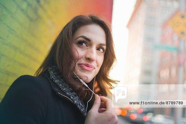Junge Frau hört Kopfhörer auf der Stadtstraße