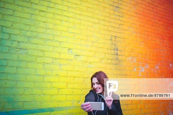 Junge Frau beim Selbstporträt neben der gelben Wand Junge Frau beim Selbstporträt neben der gelben Wand