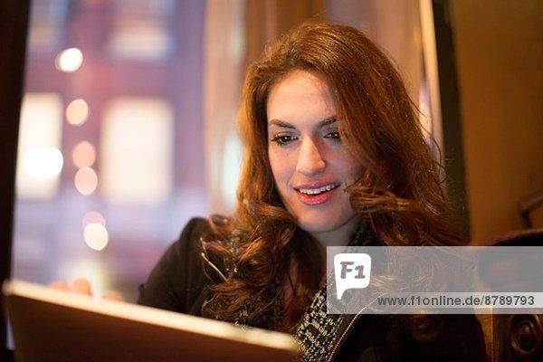 Junge Frau mit digitalem Tablett im Café