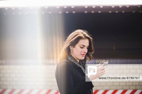Junge Frau schaut auf Handy in der U-Bahn-Station