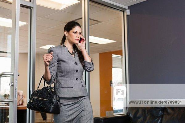 Junge Geschäftsfrau  die ihr Büro verlässt  am Telefon