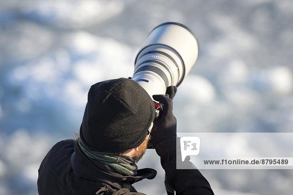 Fotograf mit Teleobjektiv  Insel Spitzbergen  Spitzbergen Inselgruppe  Svalbard und Jan Mayen  Norwegen