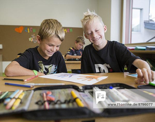 Kinder sitzen lachend in einer Volksschulklasse im Zeichenunterricht  Reith im Alpbachtal  Bezirk Kufstein  Tirol  Österreich Kinder sitzen lachend in einer Volksschulklasse im Zeichenunterricht, Reith im Alpbachtal, Bezirk Kufstein, Tirol, Österreich