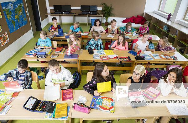 Kinder sitzen in einer Volksschulklasse beim Unterricht  Reith im Alpbachtal  Bezirk Kufstein  Tirol  Österreich