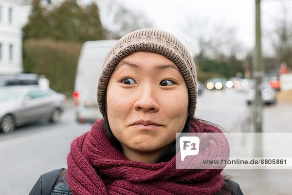 Young Asian woman wearing a burgundy scarf and a tan hat makes a face in the street.