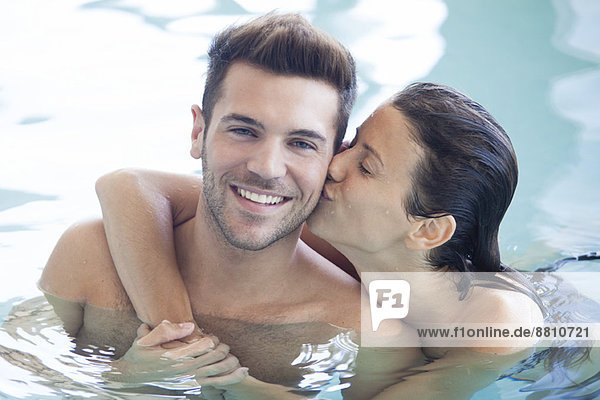 Couple relaxing together in pool  woman kissing man's cheek