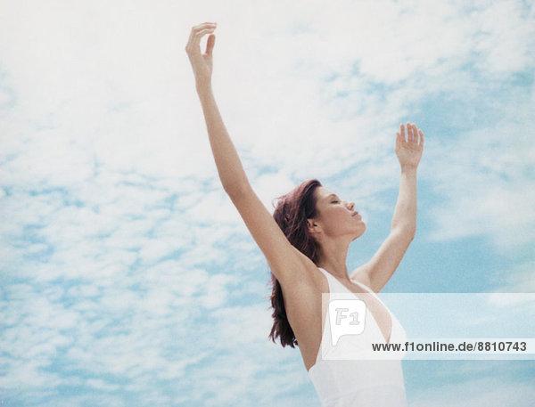 Frau im Freien stehend mit erhobenen Armen  Augen geschlossen  Blickwinkel niedrig