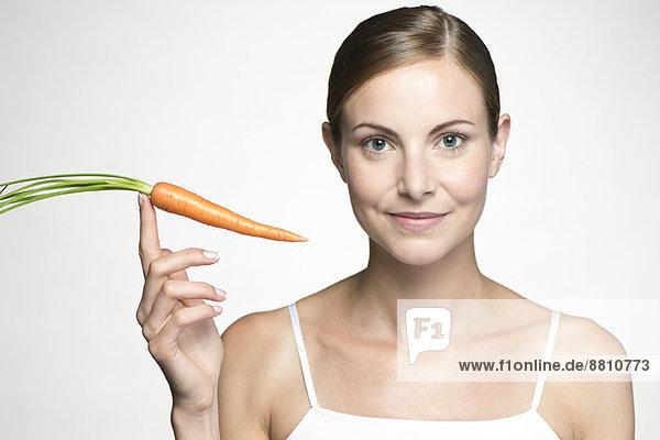 Junge Frau hält rohe Karotte hoch