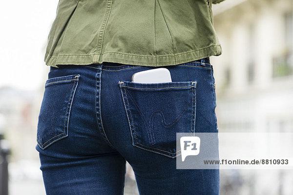Frau mit Smartphone in der Gesäßtasche