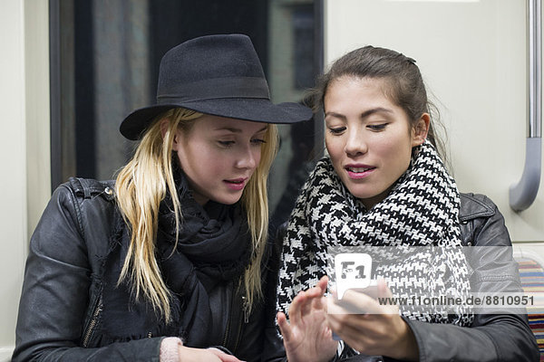 Junge Frauen sitzen zusammen in der U-Bahn und schauen auf das Smartphone.