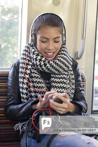 Junge Frau mit Smartphone in der U-Bahn
