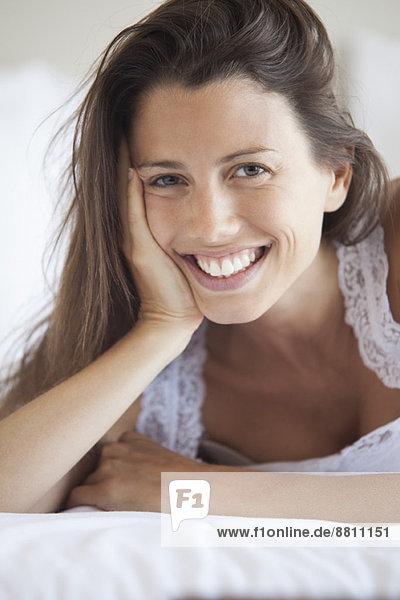 Junge Frau auf dem Bauch liegend  auf dem Ellenbogen lehnend  Portrait