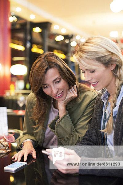 Frauen  die zusammen auf das Handy herabblicken