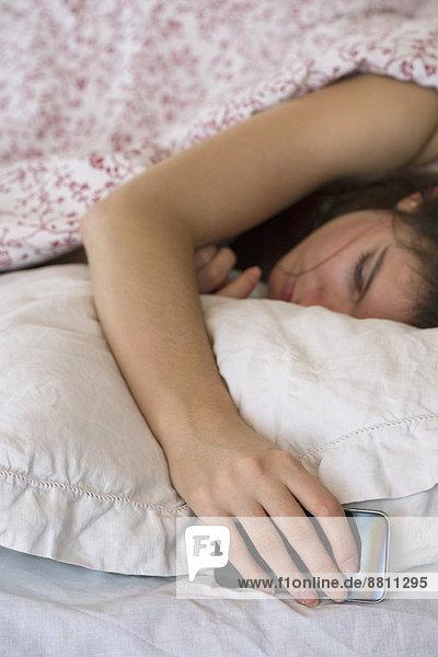 Frau schläft im Bett mit Smartphone in der Hand