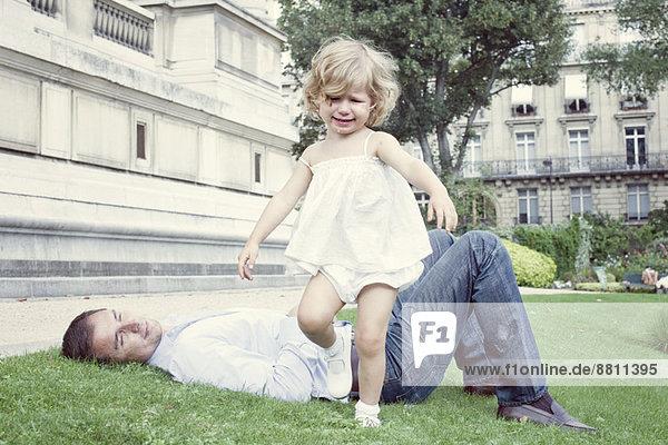 Kleinkind im Freien  Vater im Hintergrund auf Gras liegend