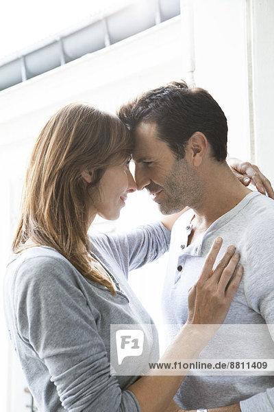 Paar berührende Nasen und Umarmung durch offenes Fenster