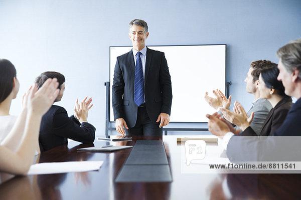 Geschäftsfreunde applaudieren Kollegen beim Treffen