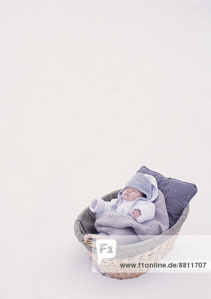 Baby schläft im Stubenwagen im Schnee Baby schläft im Stubenwagen im Schnee